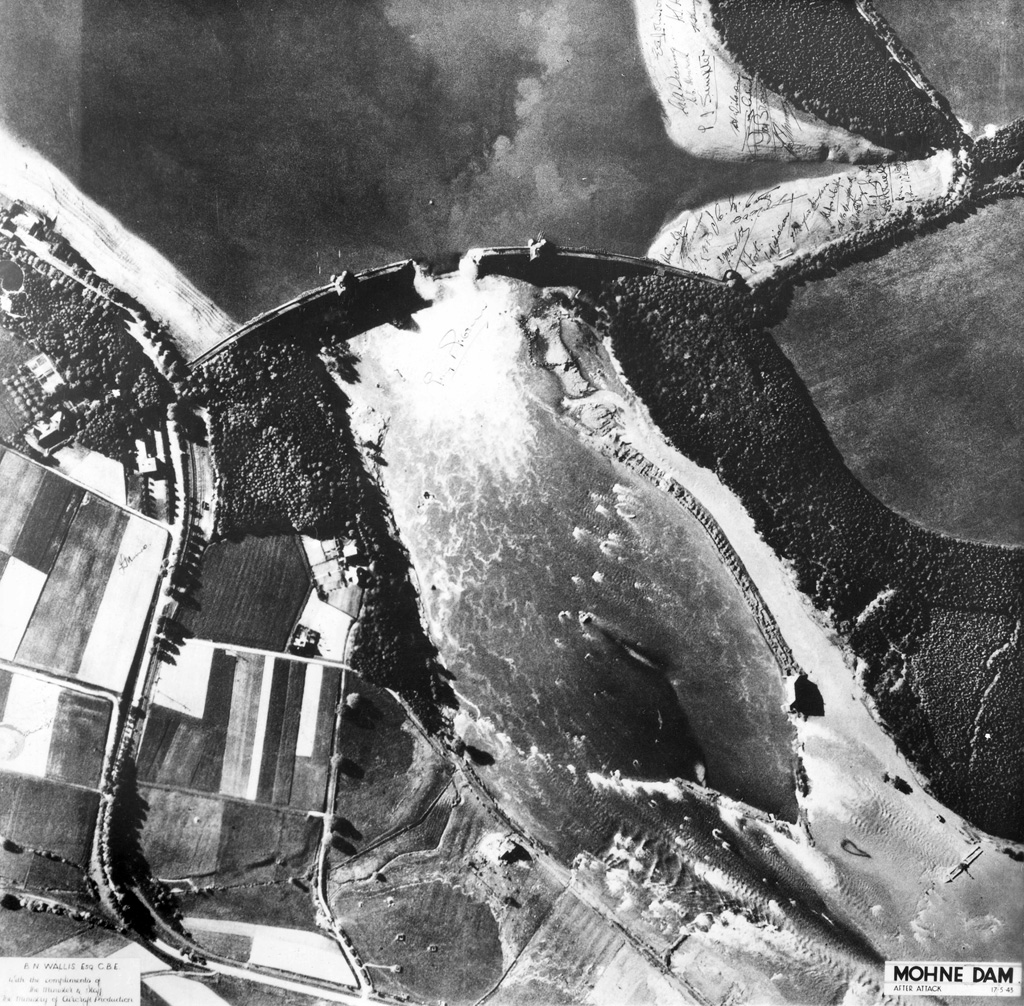 Aerial reconnaissance photograph taken on 17 May 1943 showing the breach in the Mohne Dam caused by 617 Squadron's raid during the previous night. The Eder Dam was breached by means of 'bouncing bombs' designed by Barnes Wallis. This spectacular feat of precision bombing had tremendous propaganda value, although its practical effects were less great than many had hoped © Crown Copyright